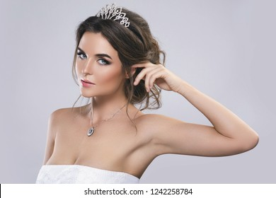 Portrait of young beautiful bride isolated on gray background