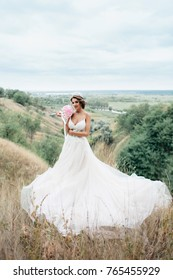 Portrait of a young beautiful bride on a background of a gorgeous view. Girl in wedding dress