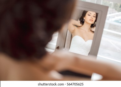 Portrait of young beautiful bride preparing to her wedding day. Gorgeous woman looking at mirror at her make-up and hairstyle