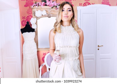 Portrait of a young beautiful bride,wearing a wedding dress,holding a glass  of champagne.