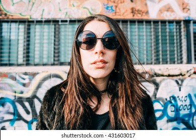 Portrait of young beautiful brown hair indie woman with septum piercing and sunglasses, looking in camera