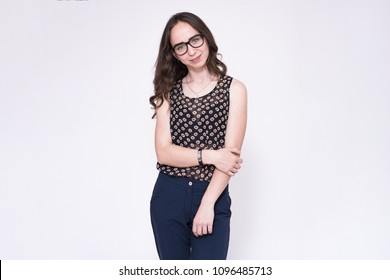 portrait of young beautiful brunette girl on white background wearing glasses. She is standing right in front of the camera and looks serious.