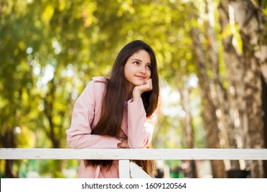Portrait of a young beautiful brunette girl in pink coat on a background of autumn park