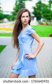 Portrait of a young beautiful brunette girl in blue dress posing in summer park