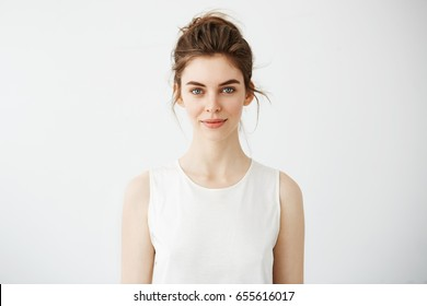 Portrait of young beautiful brunette girl smiling looking at camera over white background.