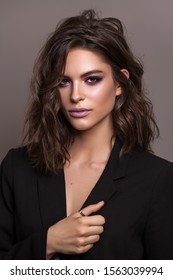 Portrait of young beautiful brunette model with violet professional make up, trendy wavy hairdo and perfect skin.
