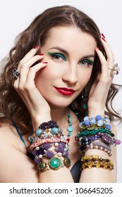 portrait of young beautiful brunette woman posing in blue dress, in beads, rings, ear-rings and bracelets on gray