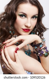 portrait of young beautiful brunette woman with manicured fingers posing in blue dress and jewelry