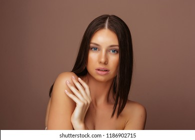 Portrait of Young Beautiful Brunette Woman with Jewelry Ring. Healthy Long Hair and Clean Skin on Grey Background
