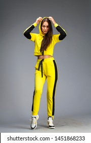 Portrait of a young beautiful brunette woman in yellow tracksuit, isolated on gray background