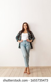 Portrait of a young beautiful brunette woman in casual clothes posing on a white background. Copy space. Vertical orientation