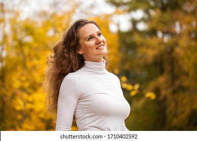 Portrait of a young beautiful brunette woman in autumn park
