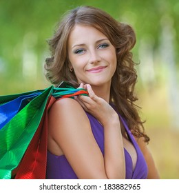 Portrait of young beautiful brunette woman wearing violet top and holding many bags at summer green park.