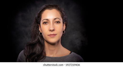 Portrait of a young beautiful brunette woman on a dark background.