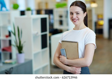 Portrait of young beautiful brunette woman smiling happily while looking at camera standing in modern office