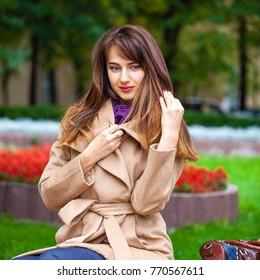 Portrait of a young beautiful brunette woman in beige coat in autumn park
