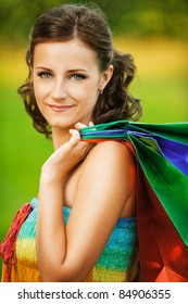 Portrait of young beautiful brunette woman wearing colourful top and holding many bags at summer green park.