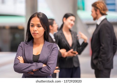 Portrait of young beautiful business woman crossed arms with  successful group of business people in the background.
