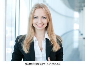 Portrait of a young beautiful business woman smiling at office building