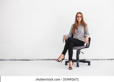 Portrait of young beautiful business woman sitting on chair against white wall.