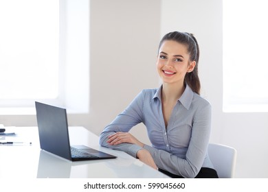 Portrait of young beautiful business woman with laptop in the office