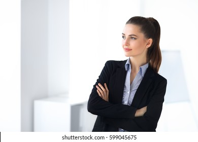 Portrait of young beautiful business woman in the office. Crossed arms