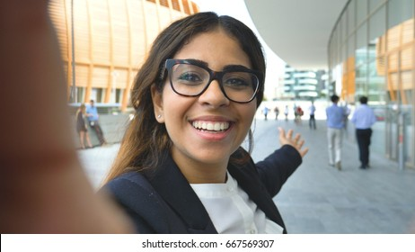 Portrait of a young beautiful business woman (student) in a suit, glasses, walking through the city, video call, selfie, holding a phone. Concept: new business, communication, Arab, banker, manager.