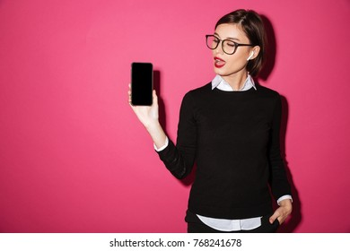 Portrait of a young beautiful businesswoman listening to music with earphones while showing blank screen mobile phone isolated over pink background