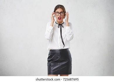 Portrait of young beautiful businesswoman tries to solve problem finds way out in her mind, looks worried and anxious. Frustrated Caucasian woman has headache as overworks every day at office