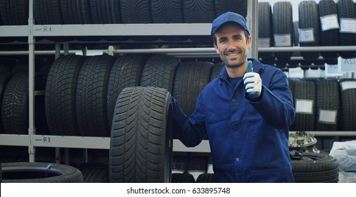 Portrait of a young beautiful car mechanic in a car service, in the background of rubber. Concept: repair of machines, fault diagnosis, repair specialist, technical maintenance and on-board computer.
