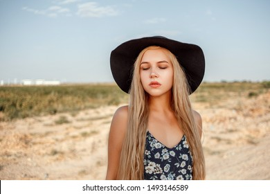 portrait of a young beautiful caucasian blonde girl in a blue dress with a floral print and a black hat standing on a sandy village road near a grape field in the summer during sunset
