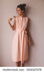 Portrait of young beautiful caucasian brunette in gorgeous peach dress. Elegant lady. Attractive woman wear pink dress with belt and hold flower. Girl look like ballerine thoughtful and dreamy.