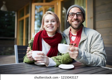 Portrait of young beautiful Caucasian couple sitting at small table on porch, holding cups of fresh coffee and smiling at camera joyfully