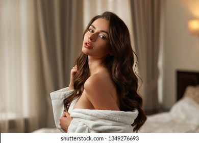 portrait of young beautiful caucasian woman with brunette wavy long hair wearing bathrobe and posing and relaxing in hotel room