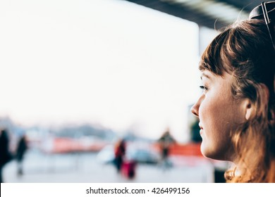 Portrait of young beautiful caucasian woman looking outside a window, smiling - thinking future, carefree, thoughtless concept