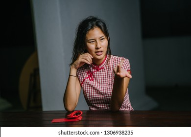 Portrait of a young and beautiful Chinese Asian girl in a traditional Chinese qipao dress. She is elegant and stylish. The millennial girl is talking and gesturing with her hands as she talks.