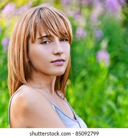 Portrait of young beautiful content blond woman at summer green park.