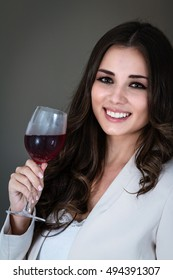 portrait of  young beautiful Costa Rican woman drinking wine wearing business attire