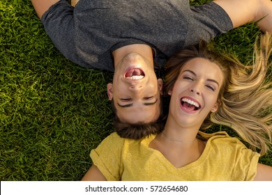 Portrait of a young beautiful couple lying on the grass