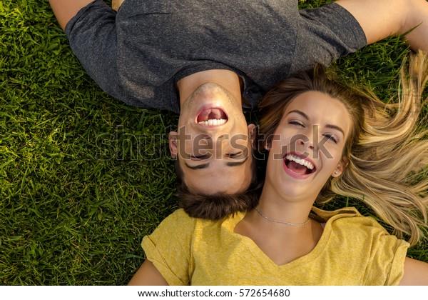 草の上に横たわる若い美しい夫婦のポートレート