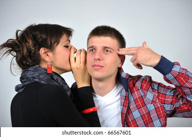 Portrait of a young beautiful couple woman is talking to the man's ear