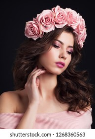 Portrait of young beautiful dark haired woman with magnificent rose wreath and gentle makeup on black background