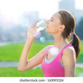 Portrait of young beautiful dark-haired woman wearing pink t-shirt drinking water after sport exercise at summer green park