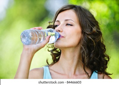 Portrait of young beautiful dark-haired woman wearing blue t-shirt drinking water at summer green park.