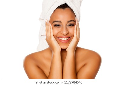 portrait of young beautiful dark-skinned woman with towel on her head, posing on a white background