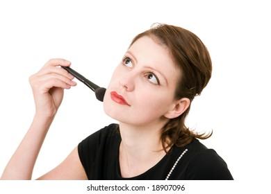 portrait of young beautiful dreaming woman holding a cosmetic brush