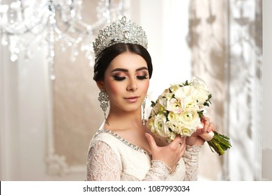 Portrait of young beautiful elegant bride with hairstyle, diamond crown and earring holding white flowers bouquet. Pretty woman with brunette hair posing in luxury interior on a sunny day