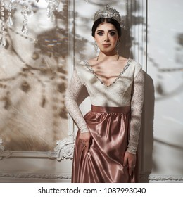 Portrait of young beautiful elegant bride with hairstyle, diamond crown and earring. Pretty woman with brunette hair posing in luxury interior on a sunny day