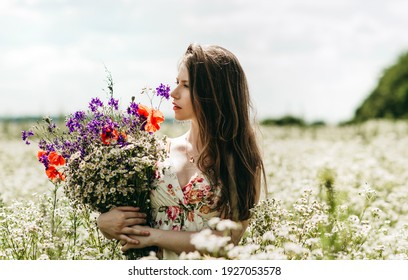 Portrait of a young beautiful European woman with long blond hair holding a bouquet of flowers outdoors in a field of daisies on a sunny summer day. Natural beauty, clean skin, makeup. Gentle girl.