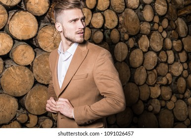 Portrait of young beautiful fashionable man in coat against wooden background.